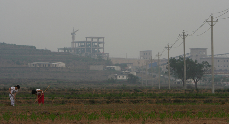 Two Chinese farmers work their farmland, located in front of a developing factory in Linfen, China. Linfen has been named by some organizations as the dirtiest city in the world.