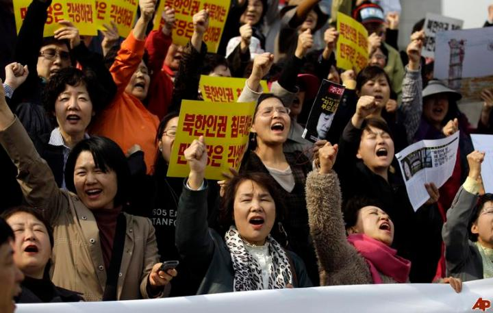North Korean defectors shout slogans in a rally demanding the improvement of North Koreans' human rights at the National Assembly in Seoul, South Korea, Thursday, April 14, 2011. About 100 protesters insisted the South Korean parliament to pass the law to help protect North Korean people's human rights. (AP Photo/Lee Jin-man)